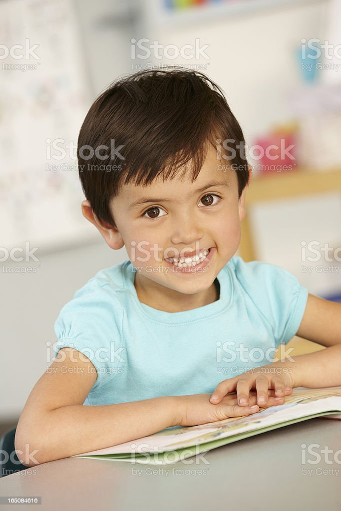 Elementary Age Schoolgirl Reading Book In Class royalty-free stock photo