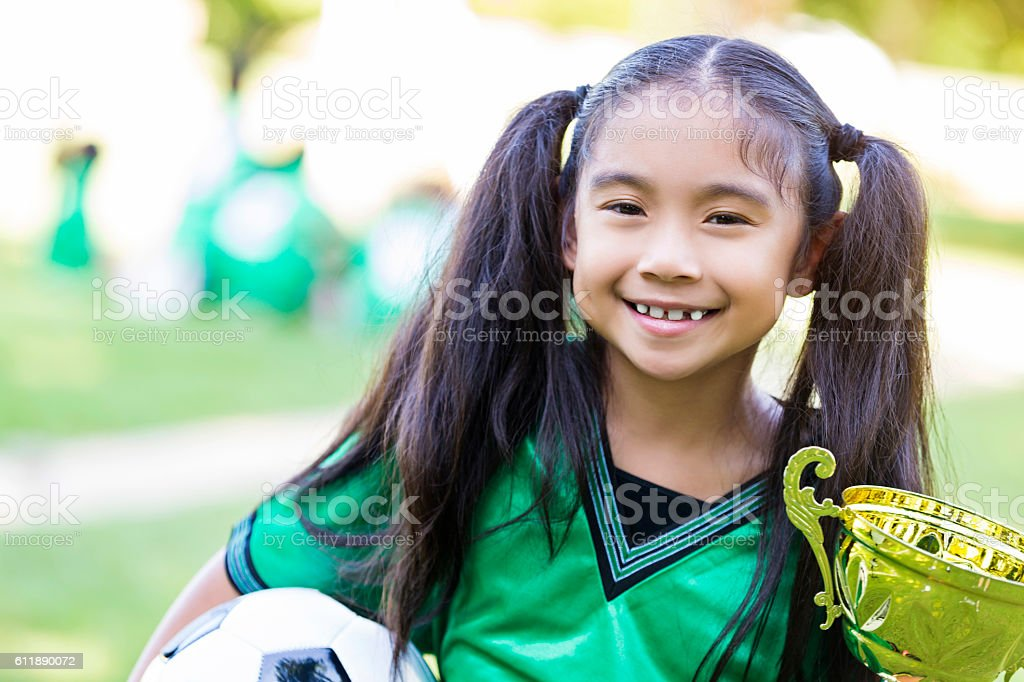 Elementary age soccer athlete holds tournament trophy stock photo