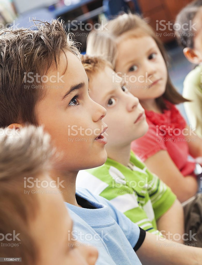 Elementary age students listening intently during story time royalty-free stock photo