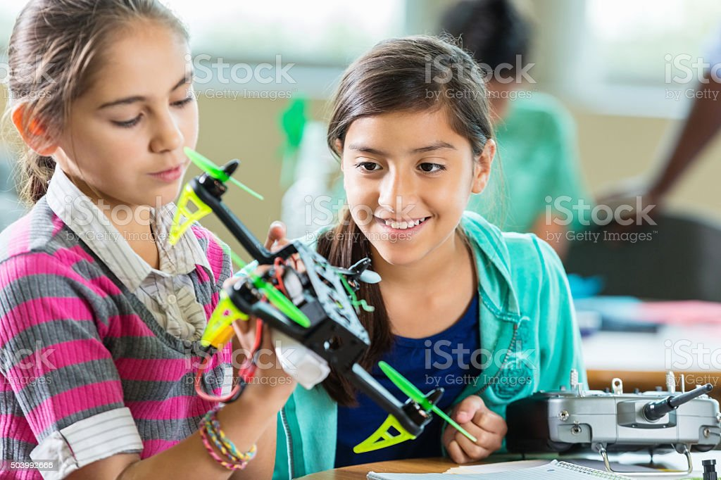 Elementary age students using drones during science technology class stock photo