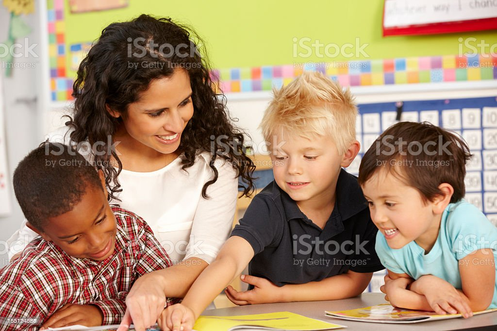 Elementary aged boys learning in classroom with teacher stock photo