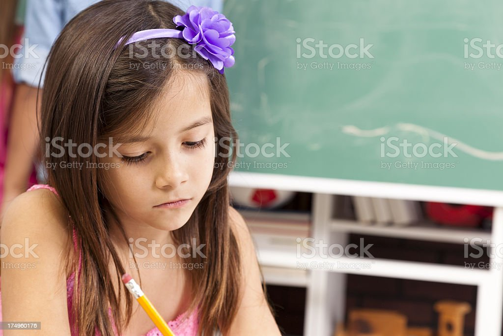 Elementary girl in classroom at desk.  Chalkboard and student background. royalty-free stock photo