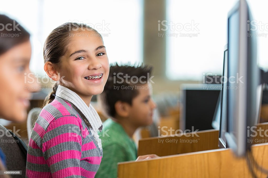 Elementary girl smiling during class in computer lab stock photo
