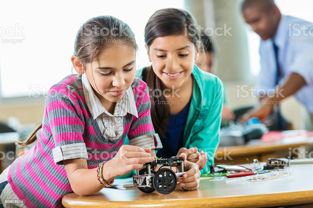 Elementary girls building robot in science and technology class stock photo