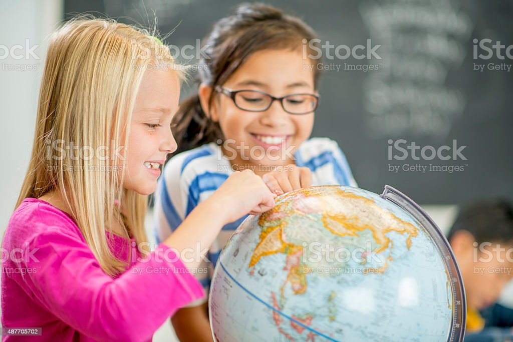 Elementary Girls Looking at a Globe stock photo