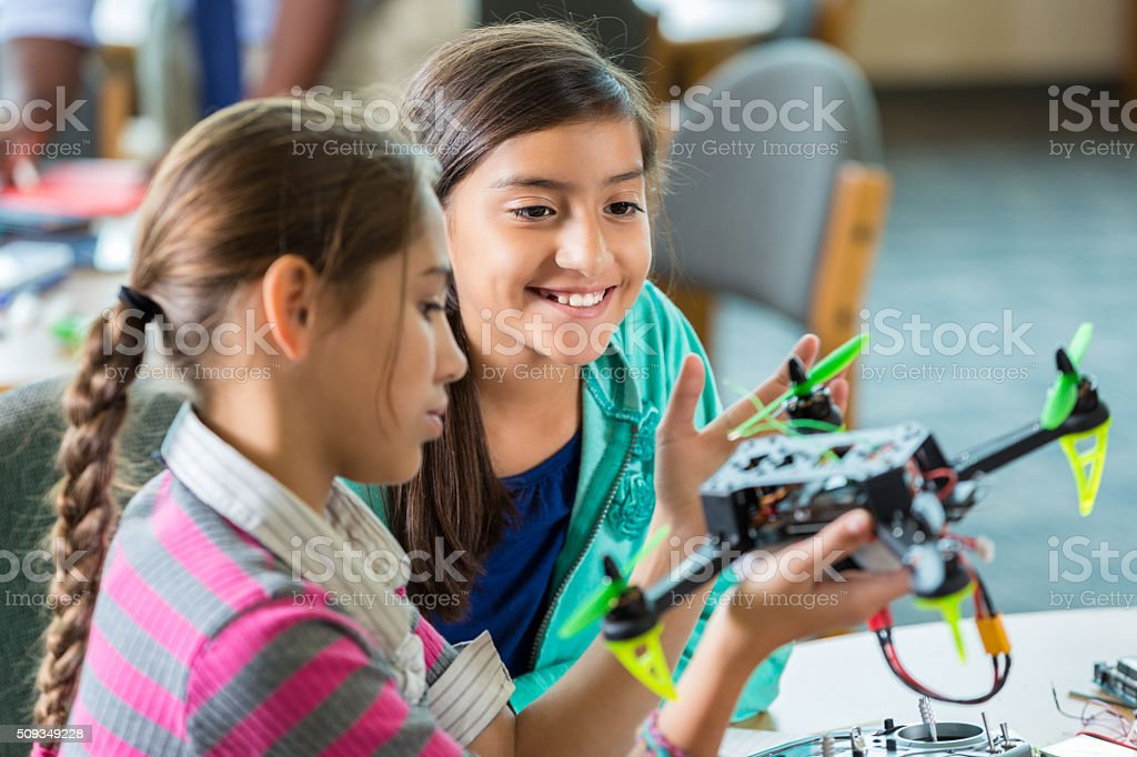 Elementary girls using drones during after school science program stock photo