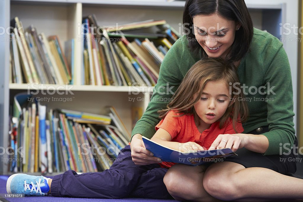 Elementary Pupil Reading With Teacher In Classroom stock photo