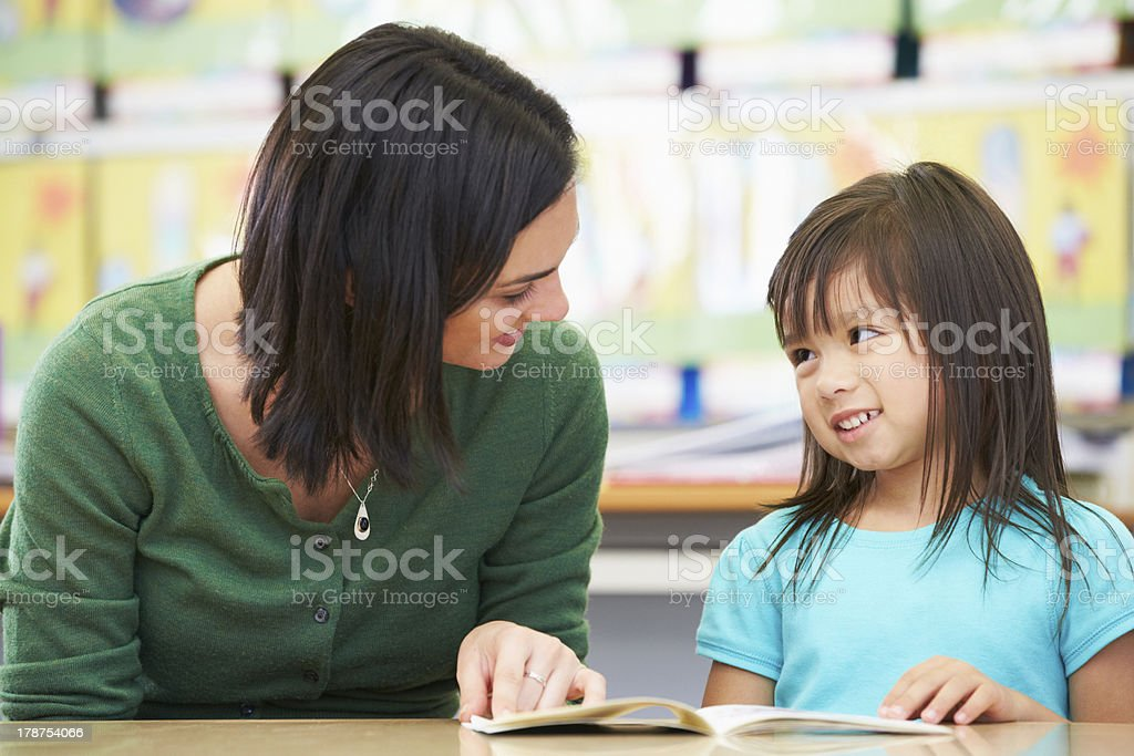 Elementary Pupil Reading With Teacher In Classroom royalty-free stock photo