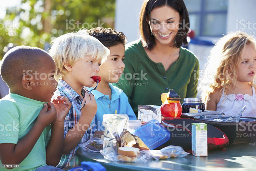 Elementary Pupils And Teacher Eating Lunch royalty-free stock photo