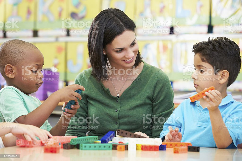 Elementary Pupils Counting With Teacher In Classroom stock photo