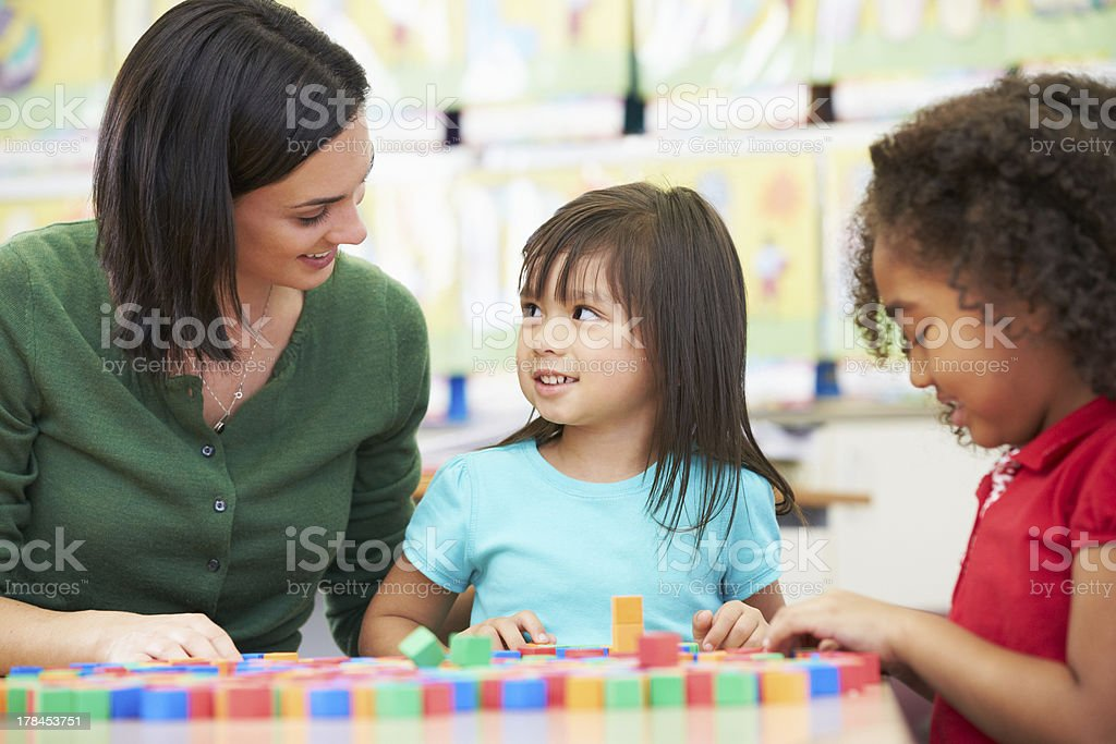 Elementary Pupils Counting With Teacher In Classroom royalty-free stock photo