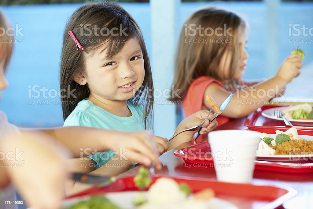 Elementary pupils enjoying a healthy lunch In the cafeteria stock photo