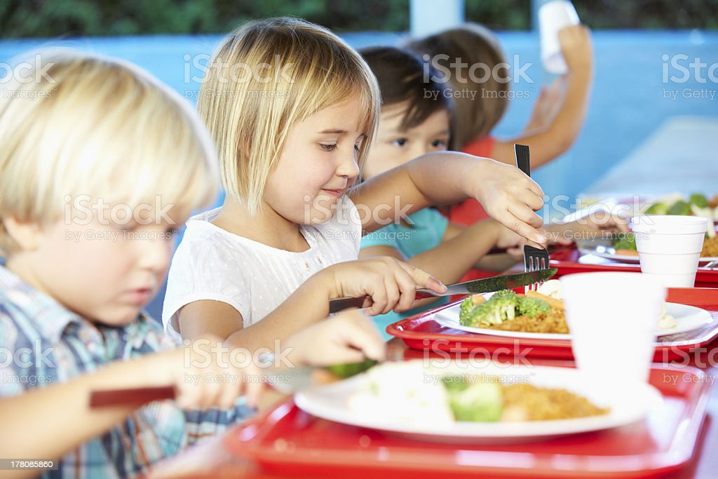 Elementary Pupils Enjoying Healthy Lunch In Cafeteria stock photo