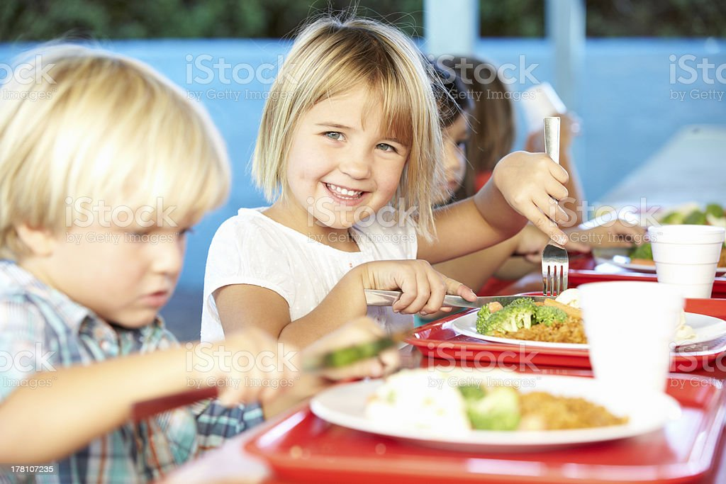 Elementary Pupils Enjoying Healthy Lunch In Cafeteria royalty-free stock photo