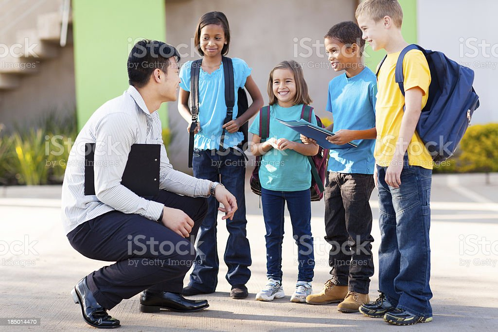 elementary pupils outside classroom talking to teacher stock photo