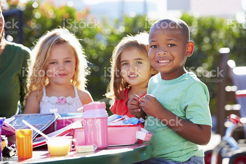 Elementary Pupils Sitting At Table Eating Lunch stock photo