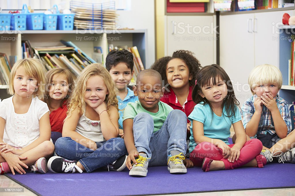 Elementary pupils sitting on the floor in a classroom stock photo