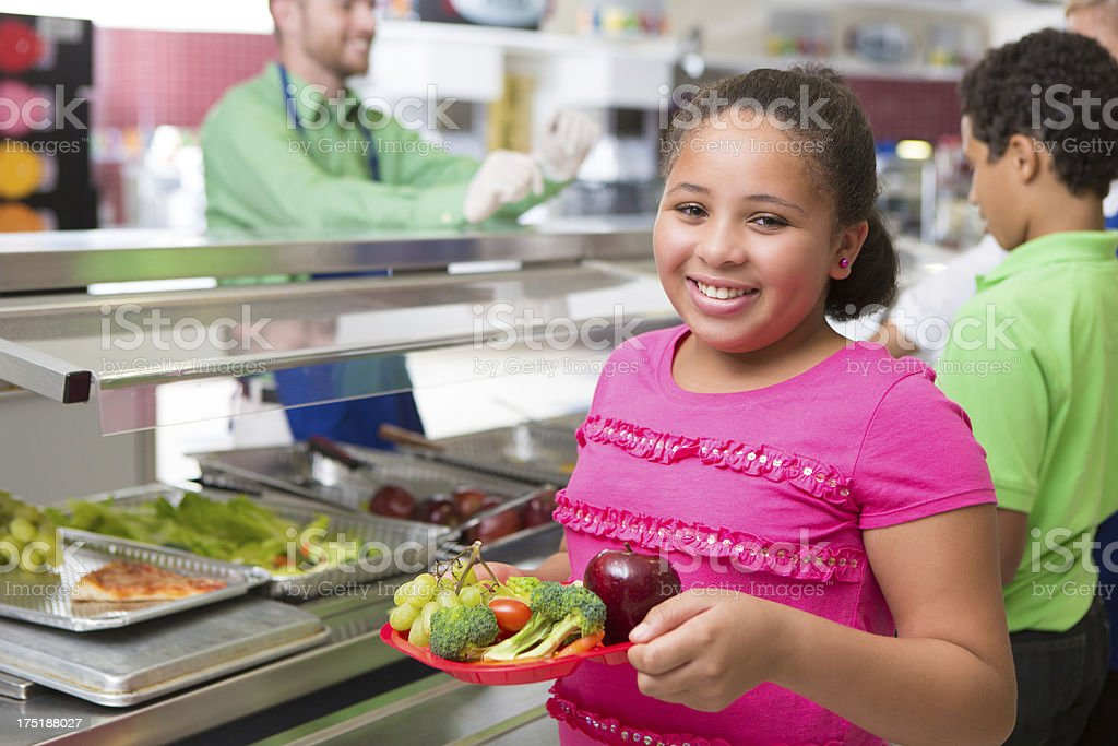 Elementary school age girl making healthy lunch choices in cafeteria stock photo