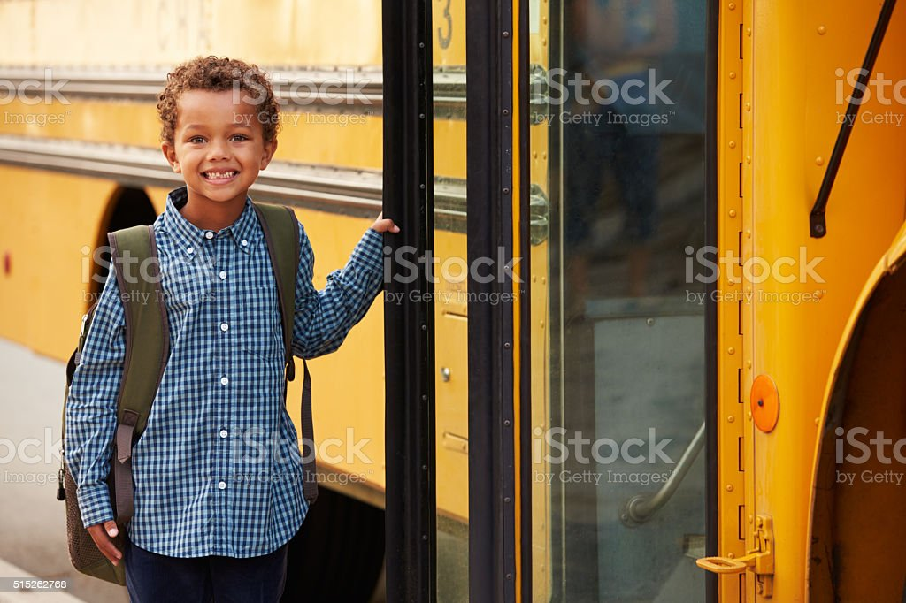 Elementary school boy getting onto a yellow school bus stock photo
