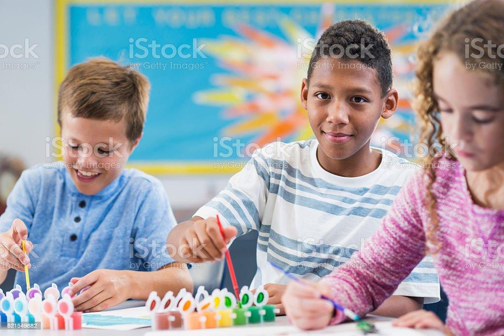 Elementary school children in art class painting stock photo