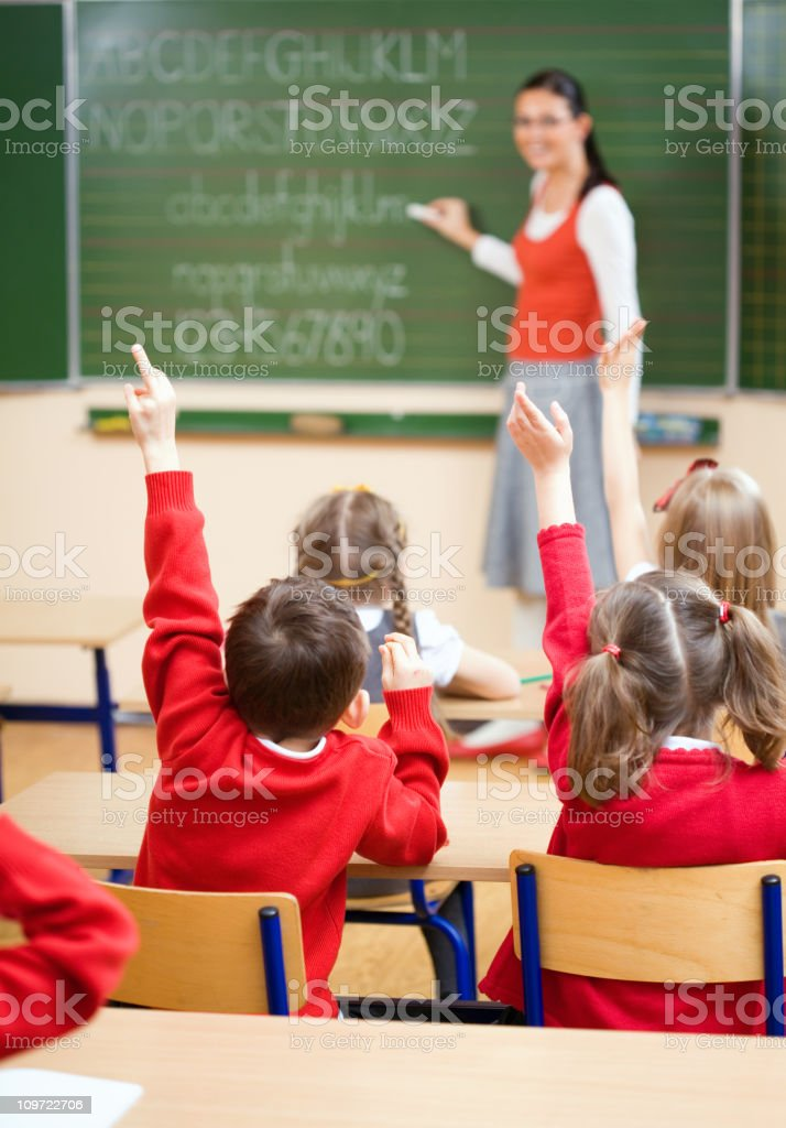 Elementary School Children Raising Hands In Class, Rear View royalty-free stock photo