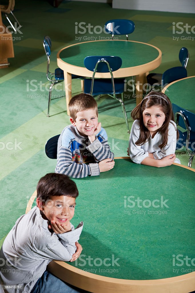 Elementary school children sitting at round table stock photo