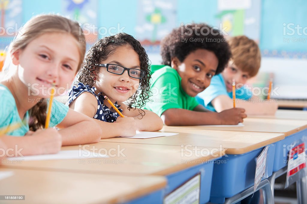 Elementary school children writing in class royalty-free stock photo