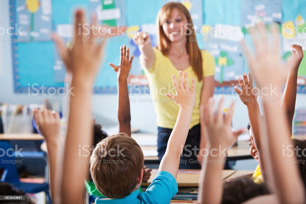 Elementary school class, raising hands stock photo