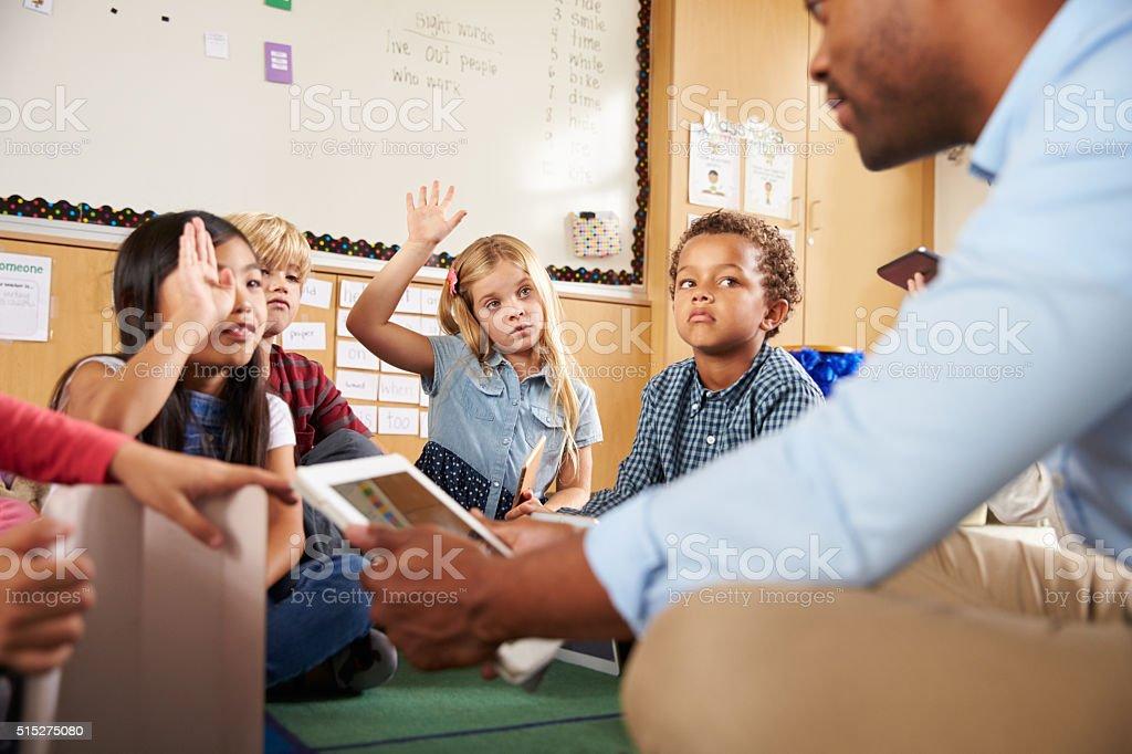 Elementary school class sitting cross legged using tablets stock photo