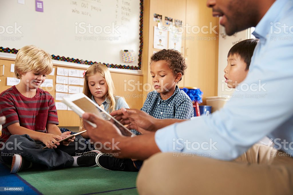 Elementary school class sitting cross legged using tablets stock photo