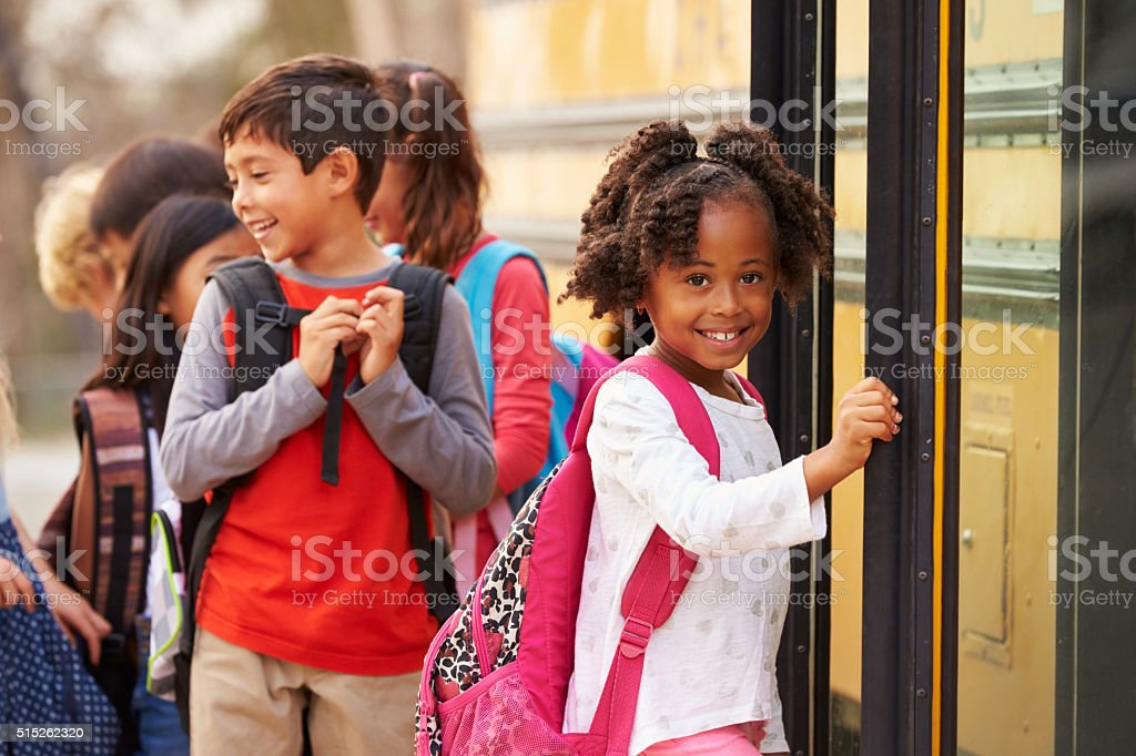 Elementary school girl at the front of the school bus queue stock photo