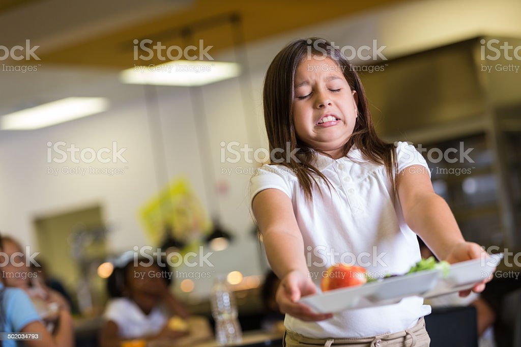 Elementary school girl disgusted by tray of healthy cafeteria food stock photo