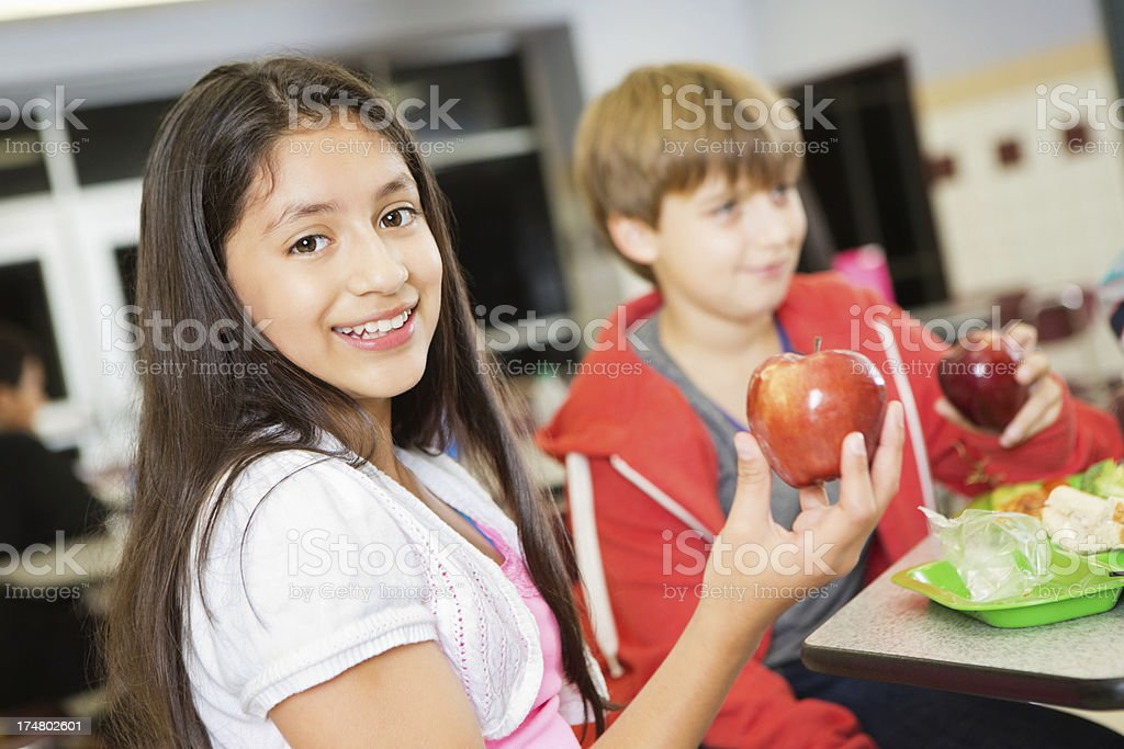 Elementary school girl eating a healthy lunch in cafeteria royalty-free stock photo