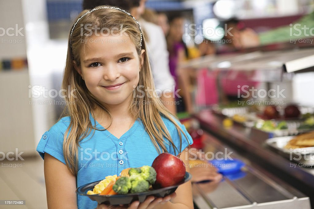 Elementary school girl with healthy lunch in cafeteria line royalty-free stock photo