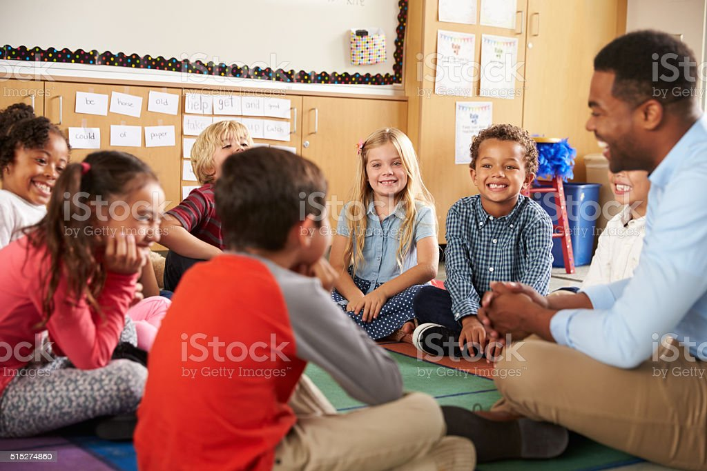 Elementary school kids and teacher sit cross legged on floor stock photo