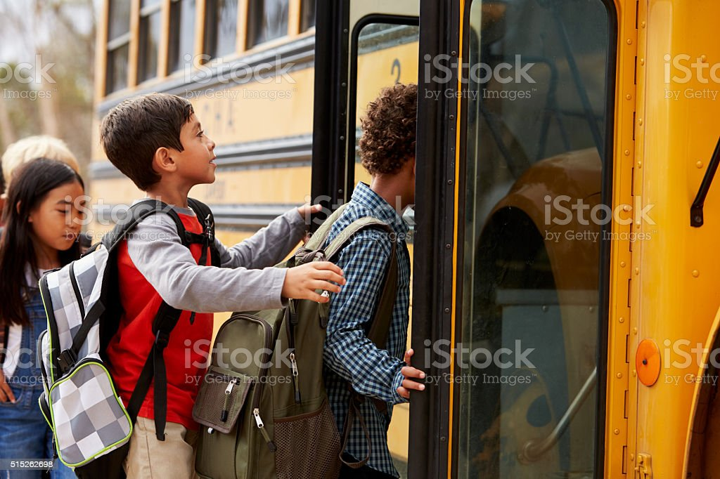 Elementary school kids climbing on to a school bus stock photo
