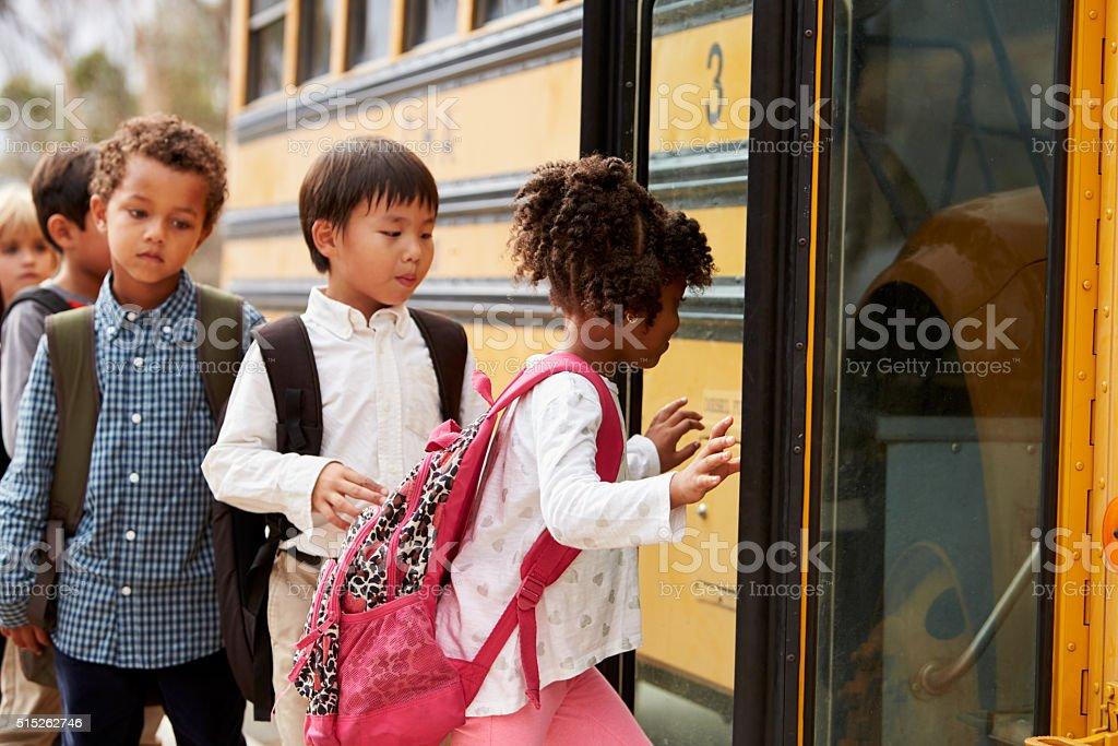 Elementary school kids climbing on to a school bus stock photo
