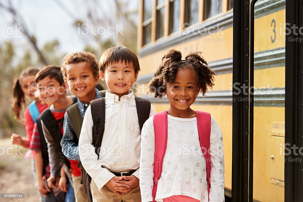 Elementary school kids queueing to get on to a school bus stock photo