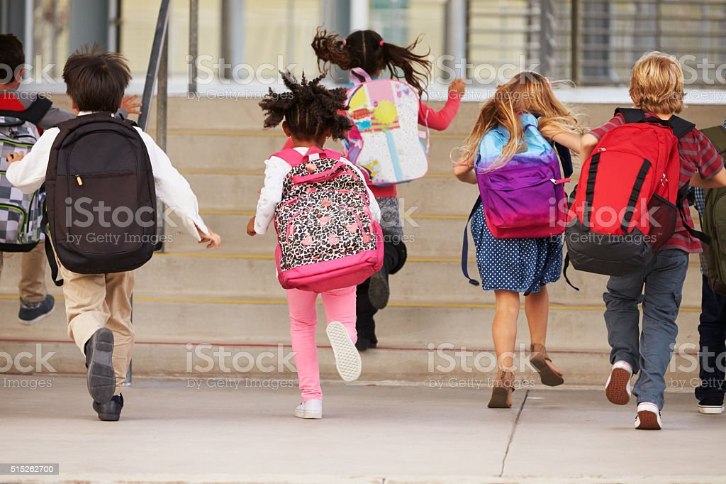 Elementary school kids running into school, back view stock photo