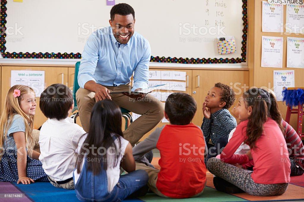 Elementary school kids sitting around teacher in a classroom stock photo