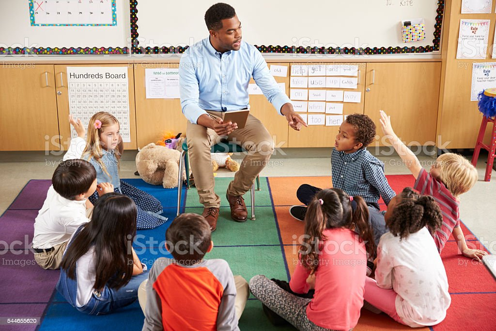 Elementary school kids sitting around teacher in a lesson stock photo