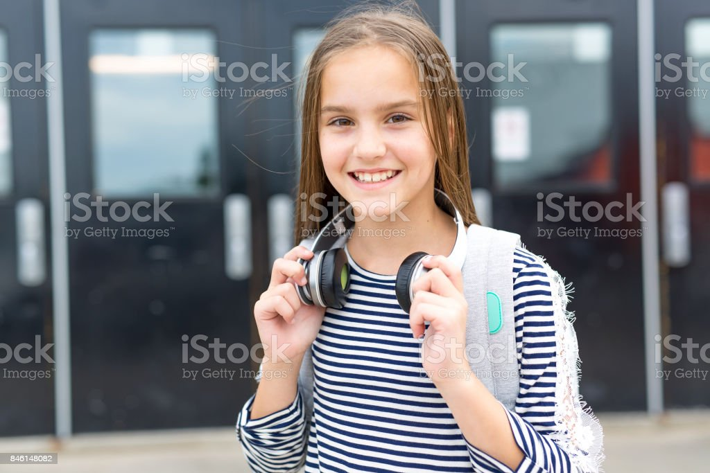 Elementary school pupil outside carrying rucksack stock photo