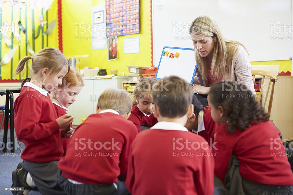 Elementary school pupils learning spelling from teacher royalty-free stock photo
