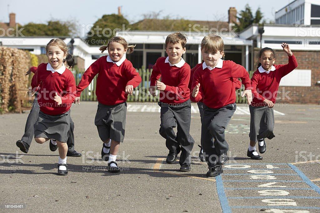 Elementary School Pupils Running In Playground stock photo