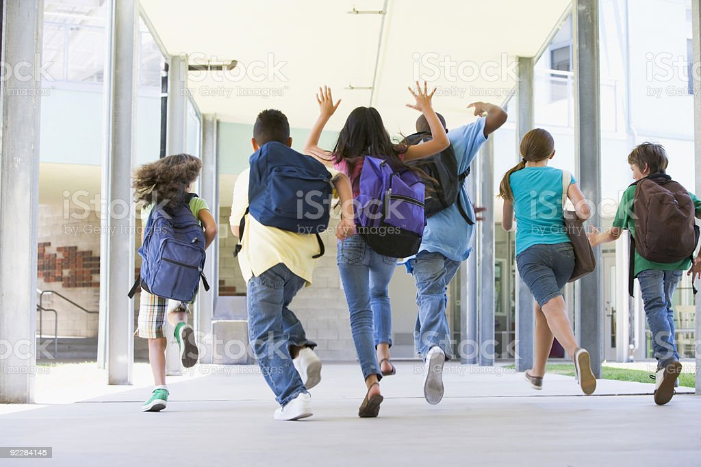 Elementary school pupils running outside stock photo