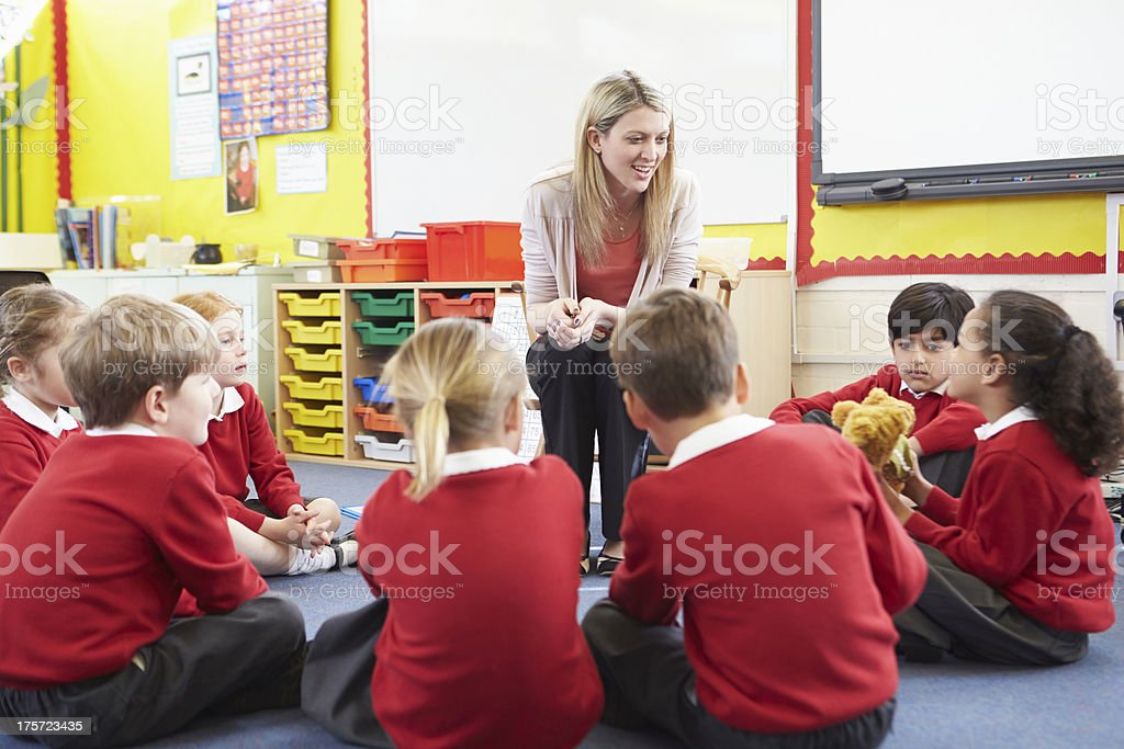 Elementary School Pupils Telling Story To Teacher royalty-free stock photo