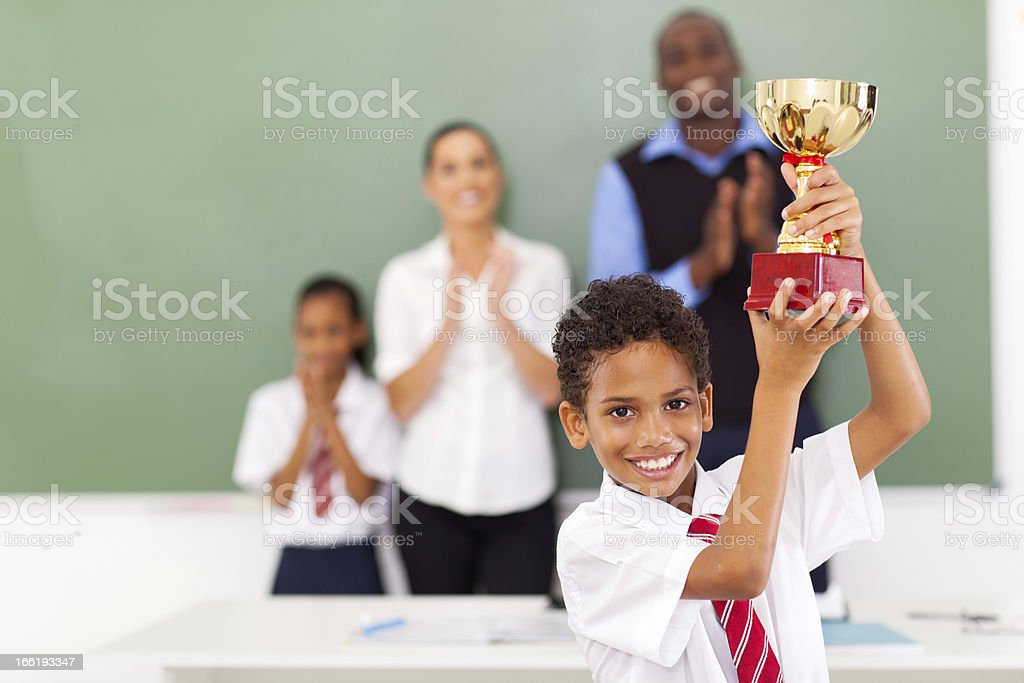 elementary school student holding a trophy stock photo