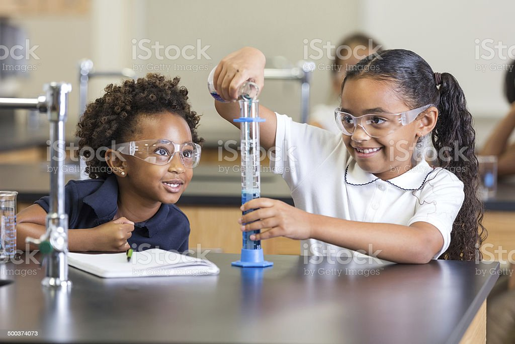 Elementary school students doing chemistry experiment in science class stock photo