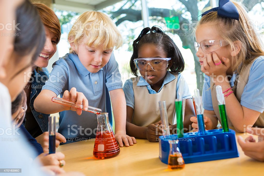 Elementary school students doing chemistry science experiment in class stock photo