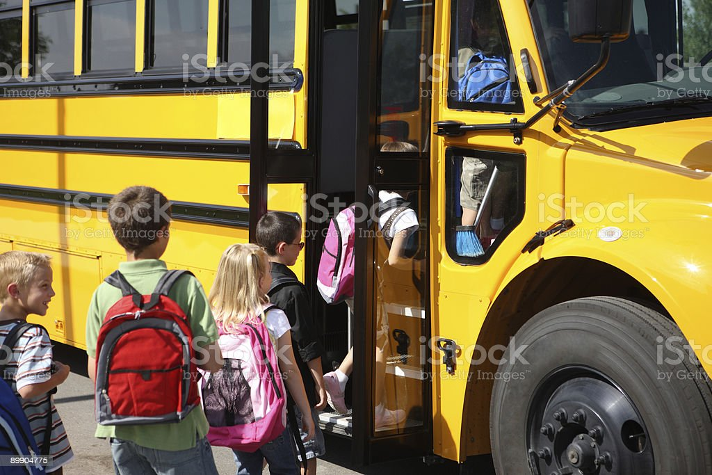 Elementary school students get on bus stock photo